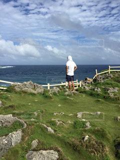 崖の上から海を眺める男性の写真・画像素材[3108306]