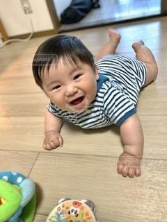 床に寝転ぶ赤ちゃんの写真・画像素材[3615877]