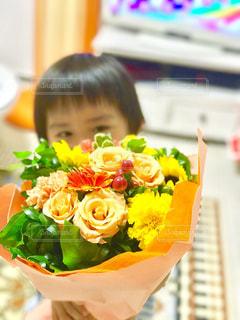 花の前のテーブルに座っている人 - No.710907