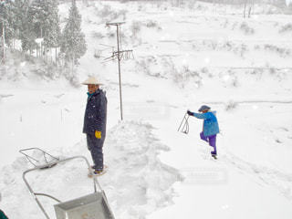 屋根の雪下ろしをする人々の写真・画像素材[1657282]