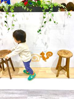 子ども,白い服,椅子,白い壁,幼児,いたずら,ホワイトカラーフォト,壁の絵のリス,壁のイラスト