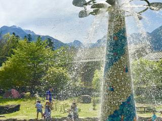 緑鮮やかな休日に水遊びをする家族の写真・画像素材[2107796]