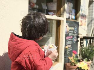 店先でドーナツを食す赤い服の子の写真・画像素材[2179610]