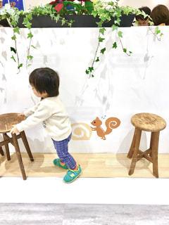 椅子を押す小さな子供にの尻尾が生えて、それをリスが押しているような壁の絵。の写真・画像素材[2230514]