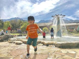 南アルプスの山々をバックに、噴水公園で水しぶきと戯れる子の写真・画像素材[2260803]