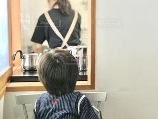 キッチンで働く後ろ姿を見つめる子供の写真・画像素材[2515095]