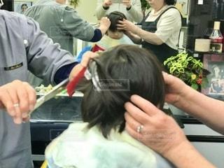 床屋で散髪。子供のじっと我慢の様子を鏡越しに見守る。の写真・画像素材[2696274]