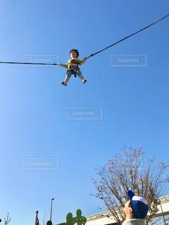 澄み渡る青空に向かって大きくジャンプの写真・画像素材[3023163]