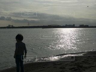夕陽の光る浜辺に名残惜しそうにたたずむ子の写真・画像素材[3395250]