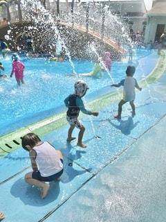 プールサイドから飛び出す噴水にはしゃぐ子供達。 焦点加工でまわりの人物が判別されないようにしています。の写真・画像素材[3557612]
