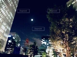 都会のビルの間から見上げる月の写真・画像素材[3924188]