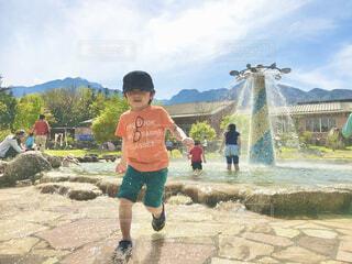 新緑の山々をバックに噴水の公園で水遊びの写真・画像素材[4371280]