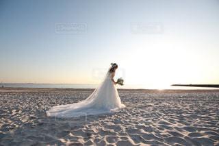 女性,1人,自然,空,花,夕日,屋外,白,砂浜,波,水面,海岸,結婚式,ドレス,ウエディング,ウエディングドレス,結婚式ドレス