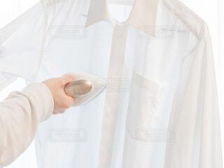 衣類スチーマーでアイロン掛けする様子の写真・画像素材[3948413]