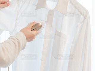 衣類スチーマーでアイロン掛けする様子の写真・画像素材[3948412]
