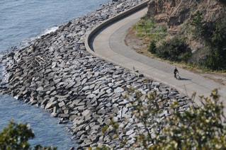 海岸べりを歩く手押し車の老婆の写真・画像素材[3108108]