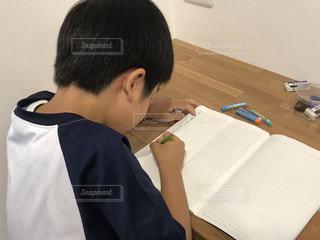 テーブルに座って宿題をしている男の子の写真・画像素材[3423033]