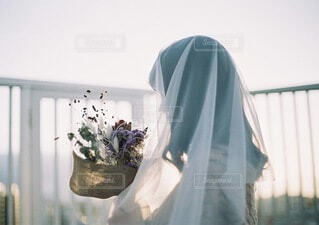 夕陽に包まれる花束を持った女性の写真・画像素材[4036656]