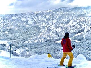 雪に覆われた山の下にスキーに乗っている男の写真・画像素材[4058128]
