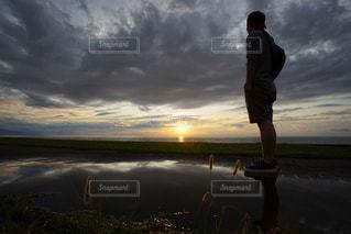 夕日の前に立っている男 海に沈む美しい夕陽と水溜りのリフレクションの写真・画像素材[3440114]