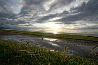 海に沈む美しい夕陽と水溜りのリフレクションの写真・画像素材[3440122]
