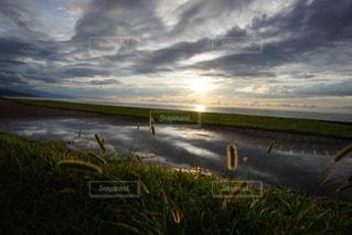 海に沈む美しい夕陽と水溜りのリフレクションの写真・画像素材[3440123]