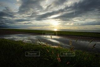 海に沈む美しい夕陽と水溜りのリフレクションの写真・画像素材[3440126]