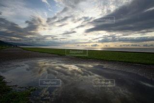 海に沈む美しい夕陽と水溜りのリフレクションの写真・画像素材[3440156]
