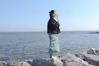 水の体の隣に立っている人の写真・画像素材[3191849]