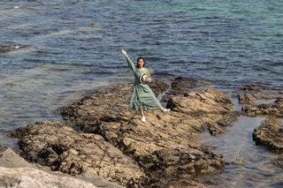 水の体の近くのビーチに立っているの写真・画像素材[3191851]
