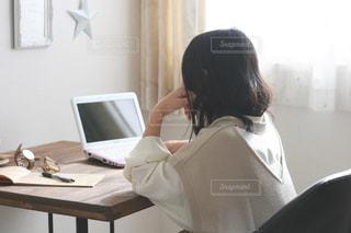 机に座っている女性の写真・画像素材[3221935]