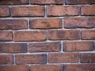 レンガの壁の前に立っている男の写真・画像素材[3164942]