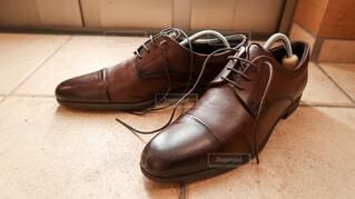 玄関でシューキーパーを入れられた茶色の革靴と自然光の写真・画像素材[4223910]