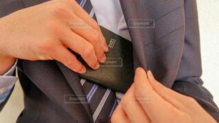 黒いスーツの内ポケットから黒い2021年用の手帳を取り出す男性の写真・画像素材[4223912]
