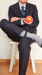 黒いスーツと青いネクタイ、灰色のソックスを身につけた男性の手の上にのったリンゴの写真・画像素材[4223914]