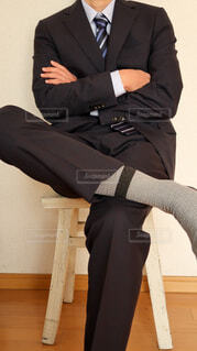 白い椅子の上で腕を組む黒いスーツ姿の男性の写真・画像素材[4223917]