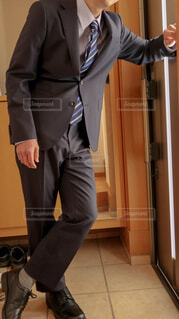 黒いスーツと革靴、青いネクタイを身につけて玄関に佇む男の写真・画像素材[4223919]