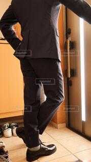 玄関で黒いスーツと革靴を身につけて決め決めのポーズをとる男の写真・画像素材[4223918]