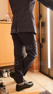 玄関の鏡の前に立ってお出かけの準備をするスーツ姿の男の写真・画像素材[4223920]
