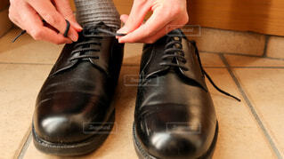 出勤のために革靴の靴紐を結ぶ手の写真・画像素材[4223921]