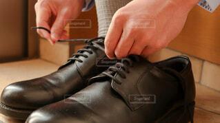 玄関で革靴を履いて出勤する朝の写真・画像素材[4223922]