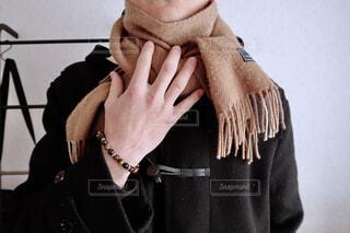 アクセサリーをつけた右手でベージュのマフラーをおさえるコートを着た男性の写真・画像素材[4256514]