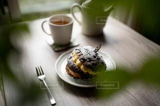 緑の向こうのテーブルの上に置いてある紅茶とチョコレートの菓子パンの写真・画像素材[4382602]