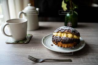 窓が差し込むテーブルの上の紅茶とチョコレートの菓子パンの写真・画像素材[4382609]