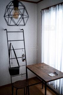 バックとランタンが掛けられたはしごとテーブルの写真・画像素材[4397694]