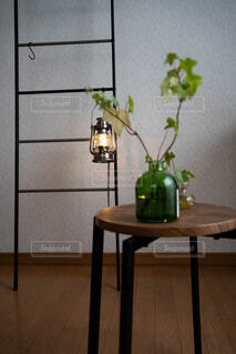 椅子の上の植物とはしごにかけられたランタンの写真・画像素材[4626534]