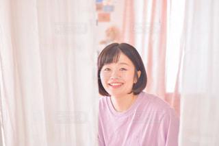 カーテンの前に立っている女性の写真・画像素材[3196427]