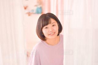 カーテンの前に立っている女性の写真・画像素材[3196428]
