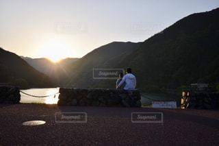 山の道の前に座っている男の写真・画像素材[1603996]