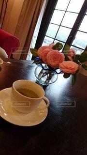テーブルの上にコーヒーと花瓶を置いたの写真・画像素材[3214908]